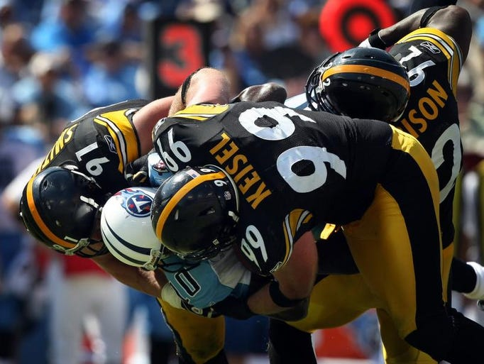 Pittsburgh Steelers defensive ends Aaron Smith (91) and Brett Keisel (99) along with linebacker James Harrison (92) slam Tennessee Titans quarterback Vince Young (10) to the ground for a sack in the third quarter at LP Field Sept. 19, 2010. The Titans lost to the Steelers 19-11.