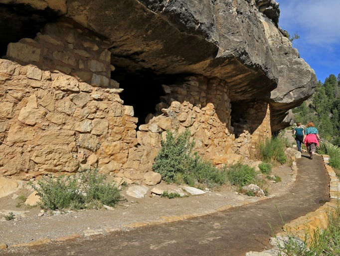 Hikers pass cliff dwellings on the Island Trail in Arizona's Walnut Canyon National Monument.