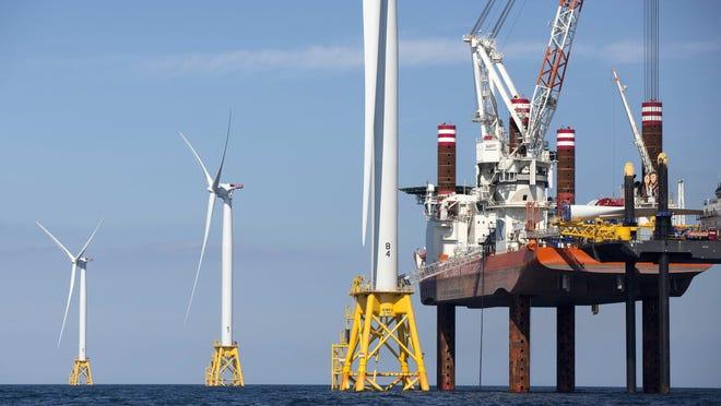 A lift boat, right, that serves as a work platform, assembles a wind turbine off Block Island, Rhode Island.