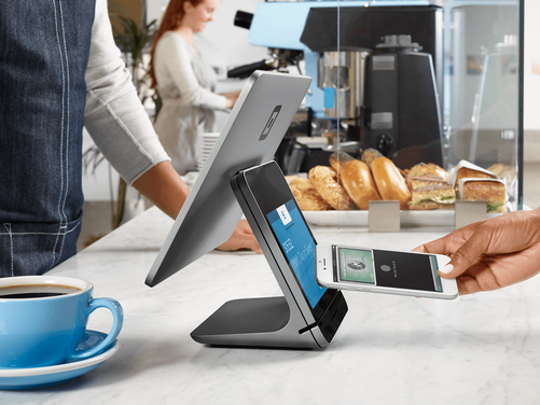 A person using Apple Pay at a Square Register.