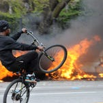 A cyclist rides by burning police cars Monday during unrest following the funeral of Freddie Gray in Baltimore. Rioters plunged part of Baltimore, torching a pharmacy, setting police cars ablaze and throwing bricks at officers.