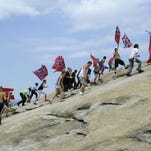 Confederate flag supporters climb Stone Mountain during a rally on Saturday in Stone Mountain, Georgia.