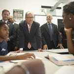 U.S. Department of Labor Secretary Tom Perez watches Construction students Vanessa Still, 22, and Kadeem Turner (right), 23, install a toilet as he tours the (HACC) Housing Authority of the City of Camden's YouthBuild program. The HACC YouthBuild program is a nonresidential, community-based alternative education program that provides classroom instruction and occupational skills training to at-risk individuals.