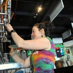 Amber Willsey pours a beer for a customer as Pisgah Brewing Co. begins to fill up on a Friday afternoon.