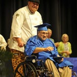 Daniel Campbell, 67, gets his hair cut by Fred Rick Longmire in preparation for his official GED ceremony.