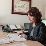 Kathy Askler works at her desk. She is the co-founder of Askler, Fitch and Associates.