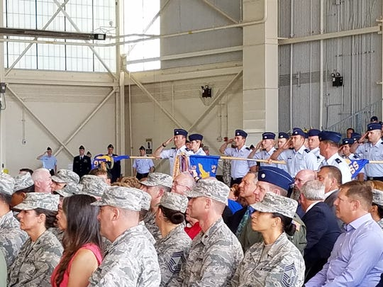 Members of the 317th Airlift Group salute Thursday in a ceremony that ended with the group reborn as the 317th Airlift Wing.