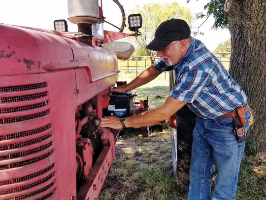 Freidi Kriftner works on an International Harvester tractor on his property in between Abilene and Oplin. Working on old tractors is a passion of Kriftner's.