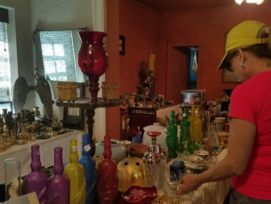 Susan King looks at glassware for sale this weekend.