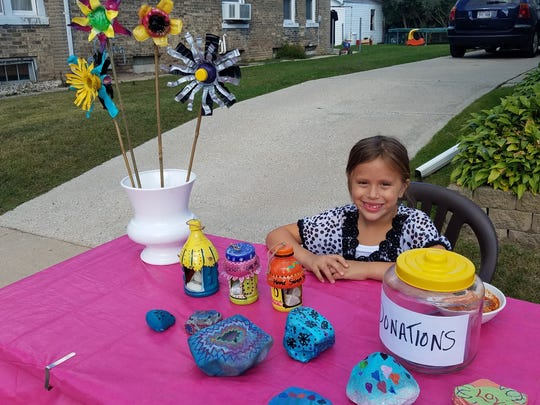 "Nadia Salinas, 7, of Manitowoc, holds a fundraiser for her 1-year-old friend Max as part of her effort titled ""Project Maxwell Rocks."""