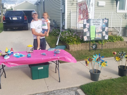 Nadia Salinas, 7, of Manitowoc, with her grandfather during a recent fundraiser for her 1-year-old friend Max.