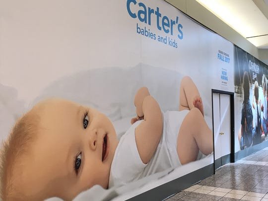 A giant baby adorns the construction barrier at Carter's,