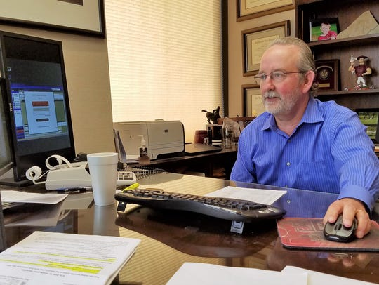 Russell Guthrie, president and CEO of Davis Kinard & Co., works at his desk. The company will become part of Eide Bailly LLC, adopting the name effective Monday.