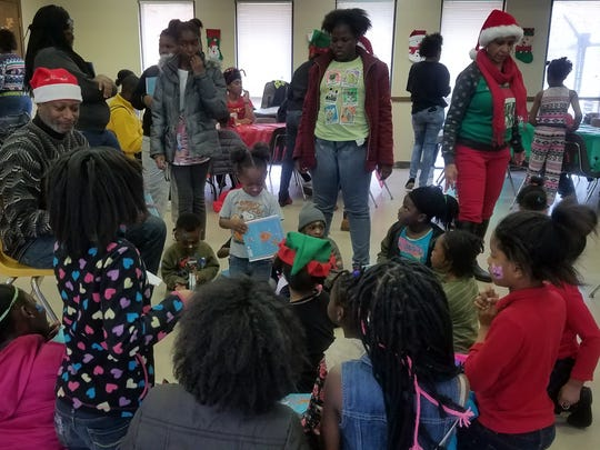 Kids read along with Jackson City Councilman Ernest Brooks, II at the 10th annual Christmas Art Celebration presented by The American Art Academy and C-MACC ArtCare and Brainbow Creative Recovery.