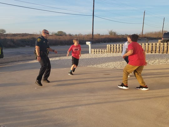Corpus Christi Police Officer Salazar laughs while playing basketball with Landon Swander, 11, and two of Landon's friends from the neighborhood on Tuesday, Jan. 30, 2018.