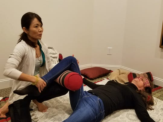 Thai Yoga Therapist, Reiki Master and Prana Practitioner Minako Davis demonstrates poses and stretches used in her sessions on PR Coordinator Lisa Ragsdale at 23 Sandstone Body and Mind Spa in Jackson.
