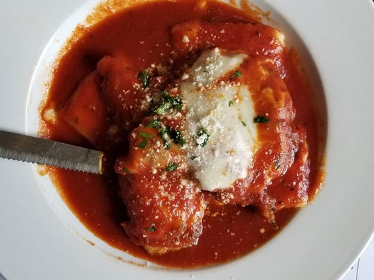 Chicken parmesan is served over housemade ravioli in