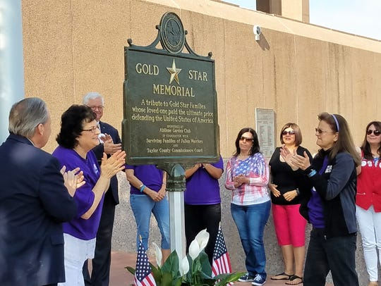 Judge Downing Bolls, Cindy McNew with the Abilene Garden Club and chaplain Donna Kleman react to the unveiling of the Gold Star Memorial, a tribute to armed forces personnel and their families. The memorial is a project of the Abilene Garden Club, Taylor County.