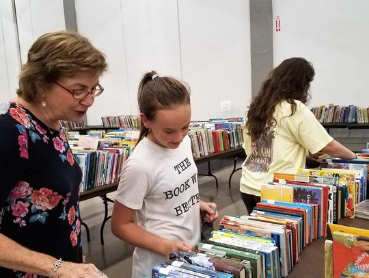 Children from the G.V. Daniels center look through books at the Friends of the Abilene Public Library Book Sale. Groups of children from the city-run program were allowed to go get some books for free before the sale.