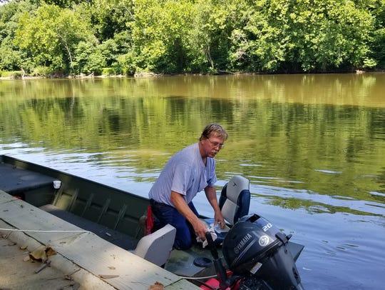 Dennis Kellar looks over his boat as he is preparing