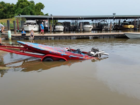 Capsized speedboat is pulled from the Red River Sunday.