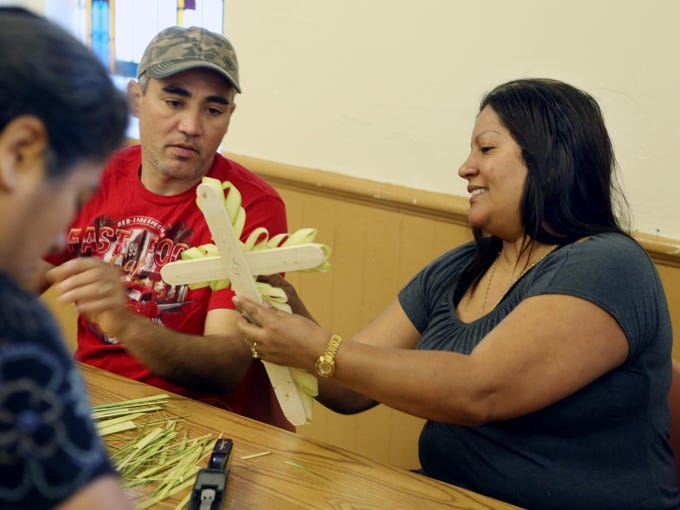 Carlos Ortiz looks at a the palm cross started by his wife, Ana, at St. Paul's Catholic Church on Saturday.