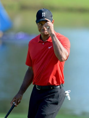Tiger Woods tips his hat to the crowd after a birdie on the 15th hole during the final round of the Wyndham Championship golf tournament at Sedgefield Country Club.