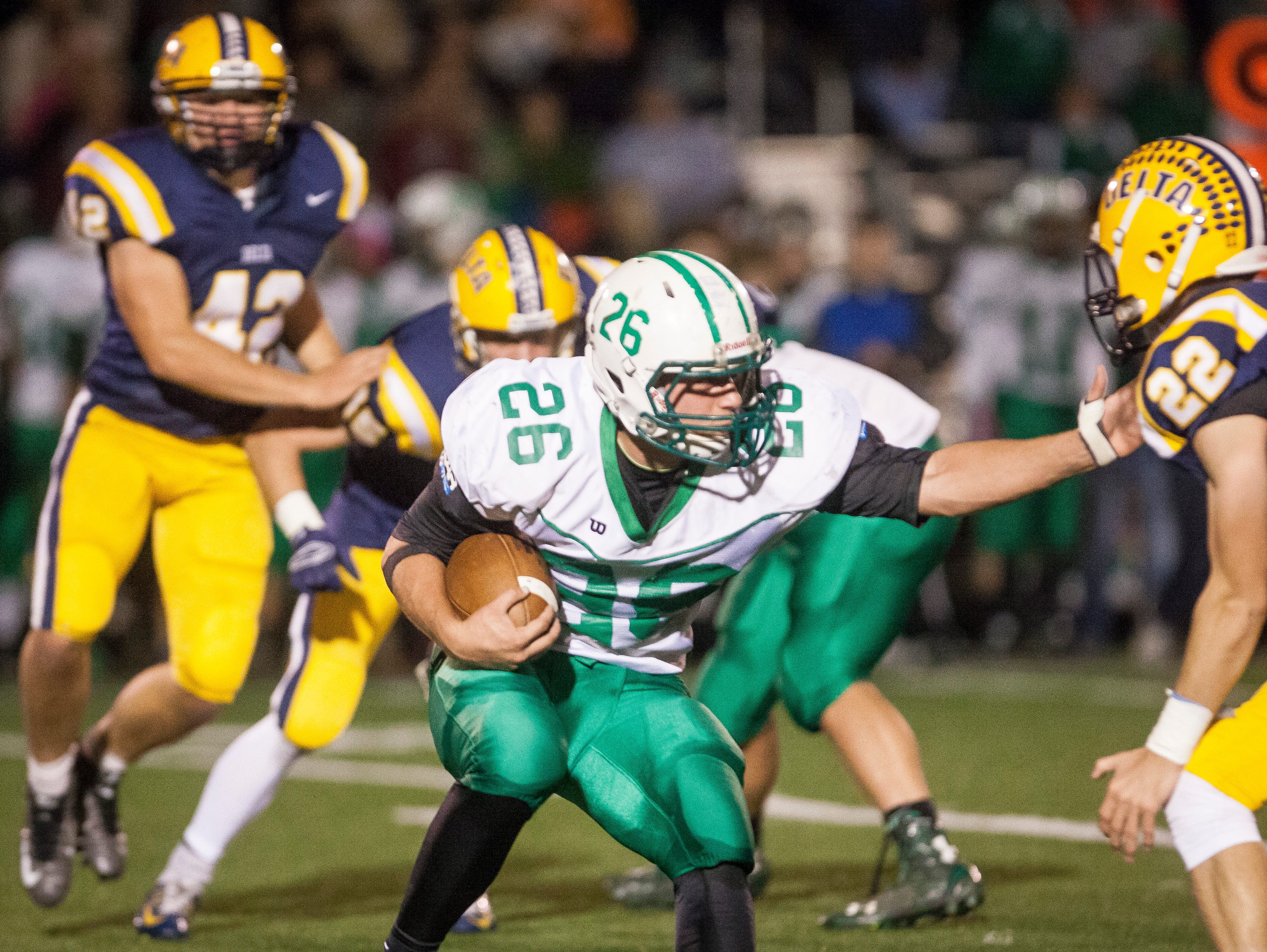 New Castle's Cody Werking tries to evade Delta defenders as he makes a run Friday night at Delta during the sectional game. Delta won 49-7.