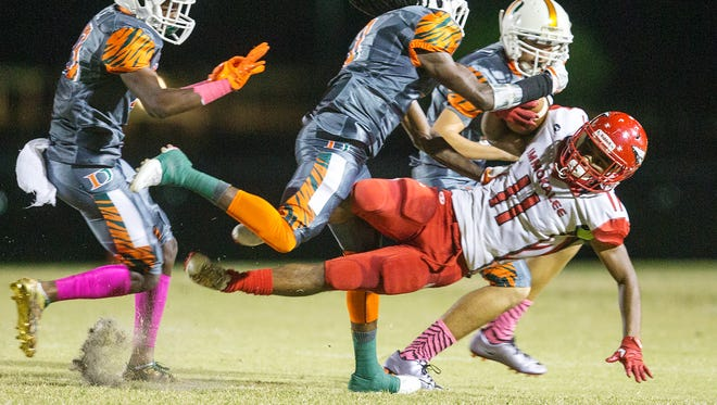 Immokalee High School's Abraham Ruiz is tackled for a loss by Dunbar defenders during second quarter play Friday at Dunbar High School in Fort Myers.