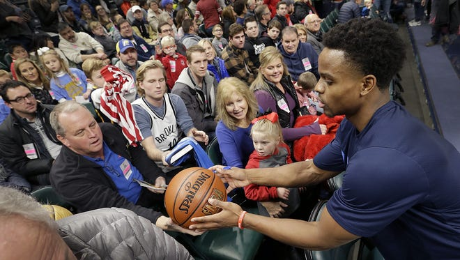 Dallas Mavericks guard Yogi Ferrell (11) greets a group of friends, fans and former teammates from Park Tudor High School before the start of their game against the Indiana Pacers at Bankers Life Fieldhouse Wednesday, Dec. 27, 2017.