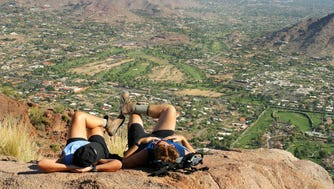 Hikers relax on the summit of Camelback Mountain, which is about 2,700 feet in elevation.