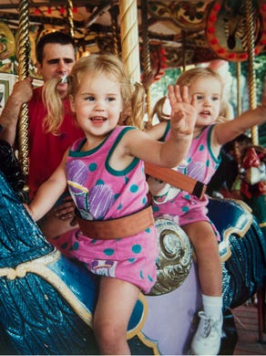 1992: Twins Day at Great Adventure, Ed Hughes standing in the background and his daughters Jennifer and Jessica 2, ride the carousel.