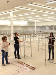 Salvation Army workers begin to assemble clothing racks
