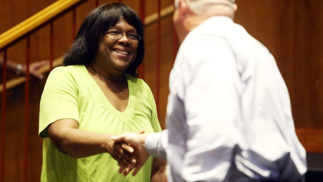 Belinda Pinkney, one of thirty-four Madison school district staffers (teachers, administrators and other employees) with more than 20 years in the district shakes hands with Madison Superintendent Dr. Michael Rossi as they were honored at Madison High School on their first day back at school. September 1, 2016, Madison, NJ