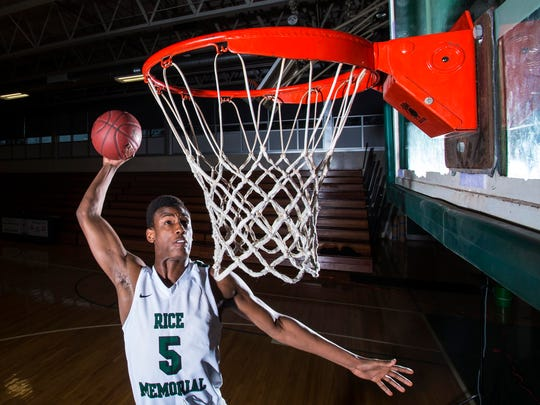 Kendrick Gray of Rice Memorial High School dunks the ball during a photo shoot in South Burlington on Monday.