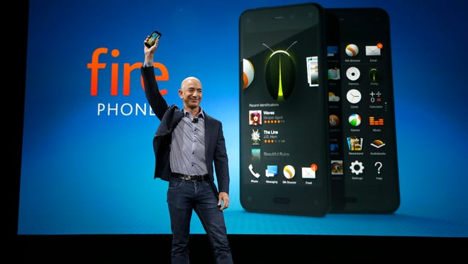 Amazon CEO Jeff Bezos holds up the new Amazon Fire Phone at a launch event in Seattle.