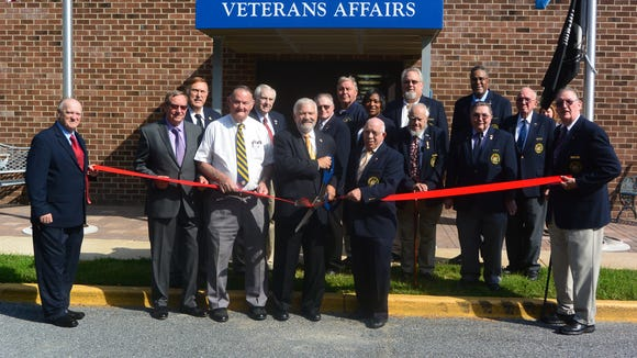 The Friends of Delaware Veterans, LLC, cut the ribbon on its new office Tuesday morning at the Commission of Veterans Affairs in Dover. Preparing to cut the ribbon to acknowledge the group's membership in the Central Delaware Chamber of Commerce, is Dave Skocik, president. To his right are Paul Davis, Friends vice president and John Knotts, executive director of the Commission of Veterans Affairs. To his left, is Paul Lardizzone, the commission chairman. Posing behind are members of the Delaware Commission of Veterans Affairs. The Friends raise funds for the Delaware Veterans Trust Fund.