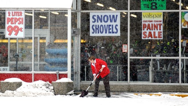An employee at Benny's on New London Turnpike in Norwich, Conn., clears snow from the store's entrance.