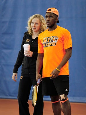 Krystina Barnum, left, talks with RIT men's tennis team captain Amos Baptiste during practice in Gordon Field House. Barnum is the tennis coach for both the women's and men's teams.