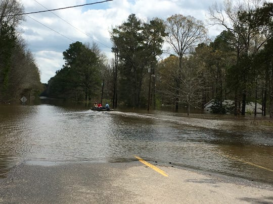 A group of men travel by boat Sunday down Highway 500 east of Georgetown to check on homes in a flooded area of Grant Parish.