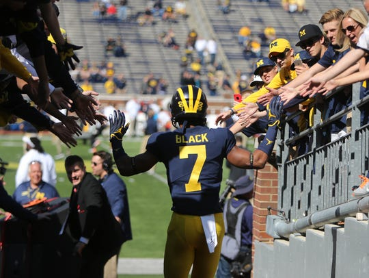 Michigan's Tarik Black high-fives fans on his way to