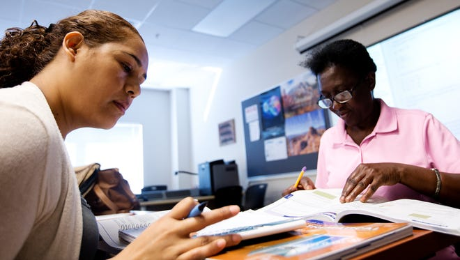 Rosalba Tello, left, works on math problems May 6, 2014, while studying for her GED at Lee County School District headquarters in Fort Myers, Fla.  On the right is Claudette Alexander. She recently passed the GED and is still studying to keep up.