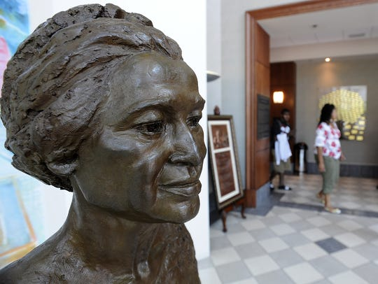 Students walk by a bust of Rosa Parks at the Rosa Parks