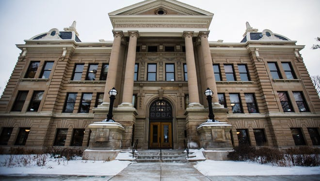 The Ingham County Courthouse stands poignantly in the center of downtown Mason, Michigan on a snowy winter day.