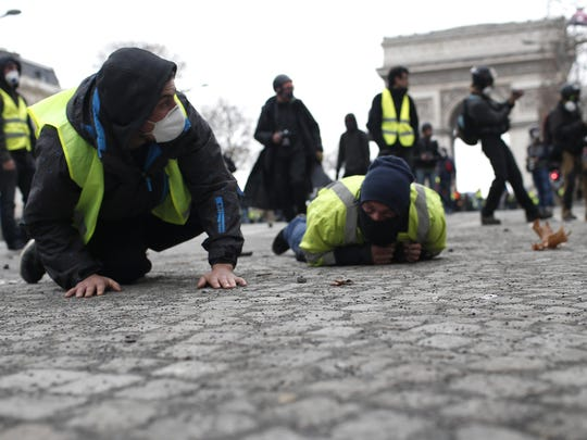 Demonstrators drop flat to the ground on the Champs-Elysees avenue during a protest Saturday, Dec. 8, 2018 in Paris.