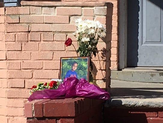 A photo of Dariel Sosa, 9, and flowers at a makeshift
