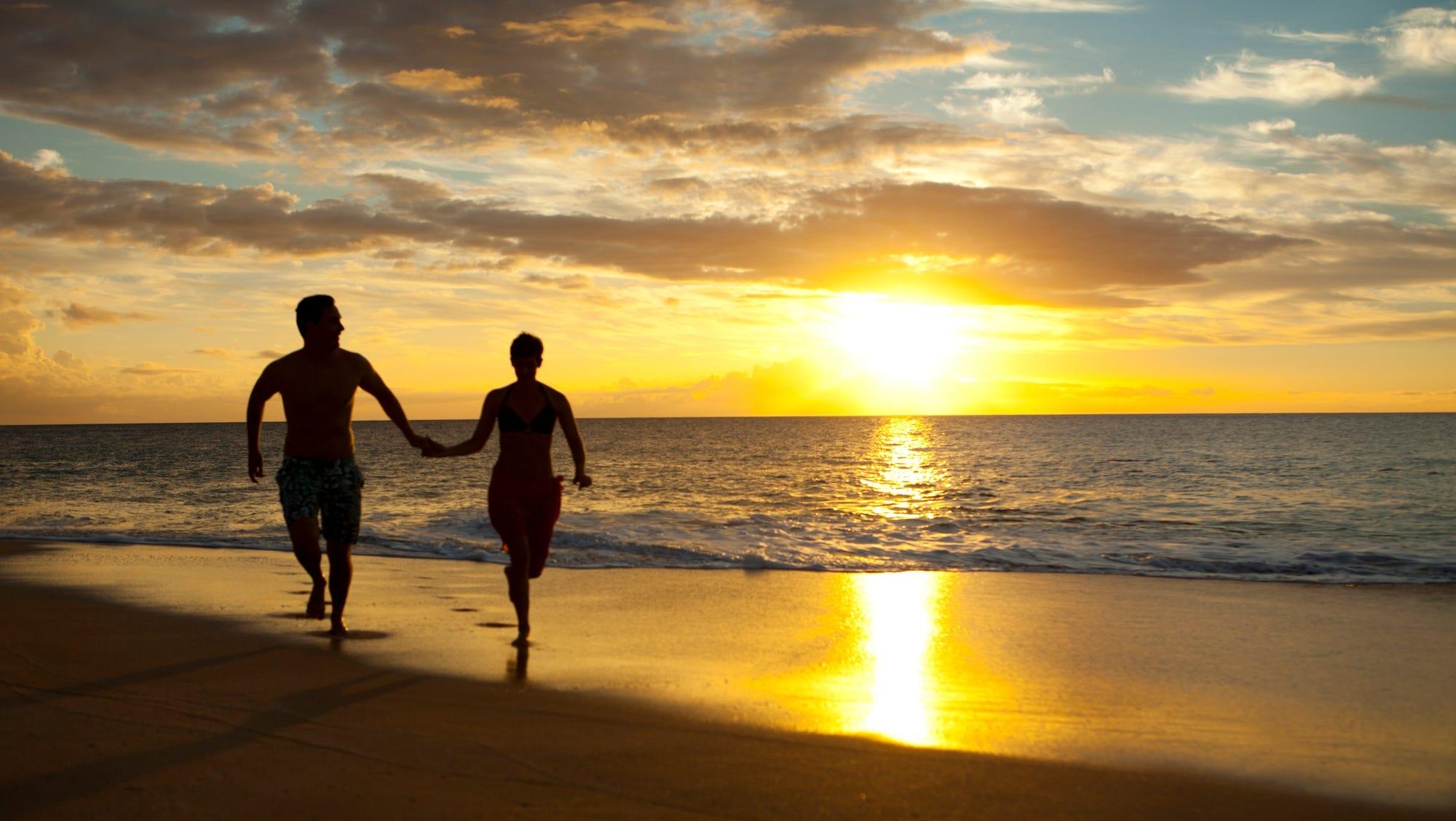 A couple runs along Papohaku Beach on Molokai.