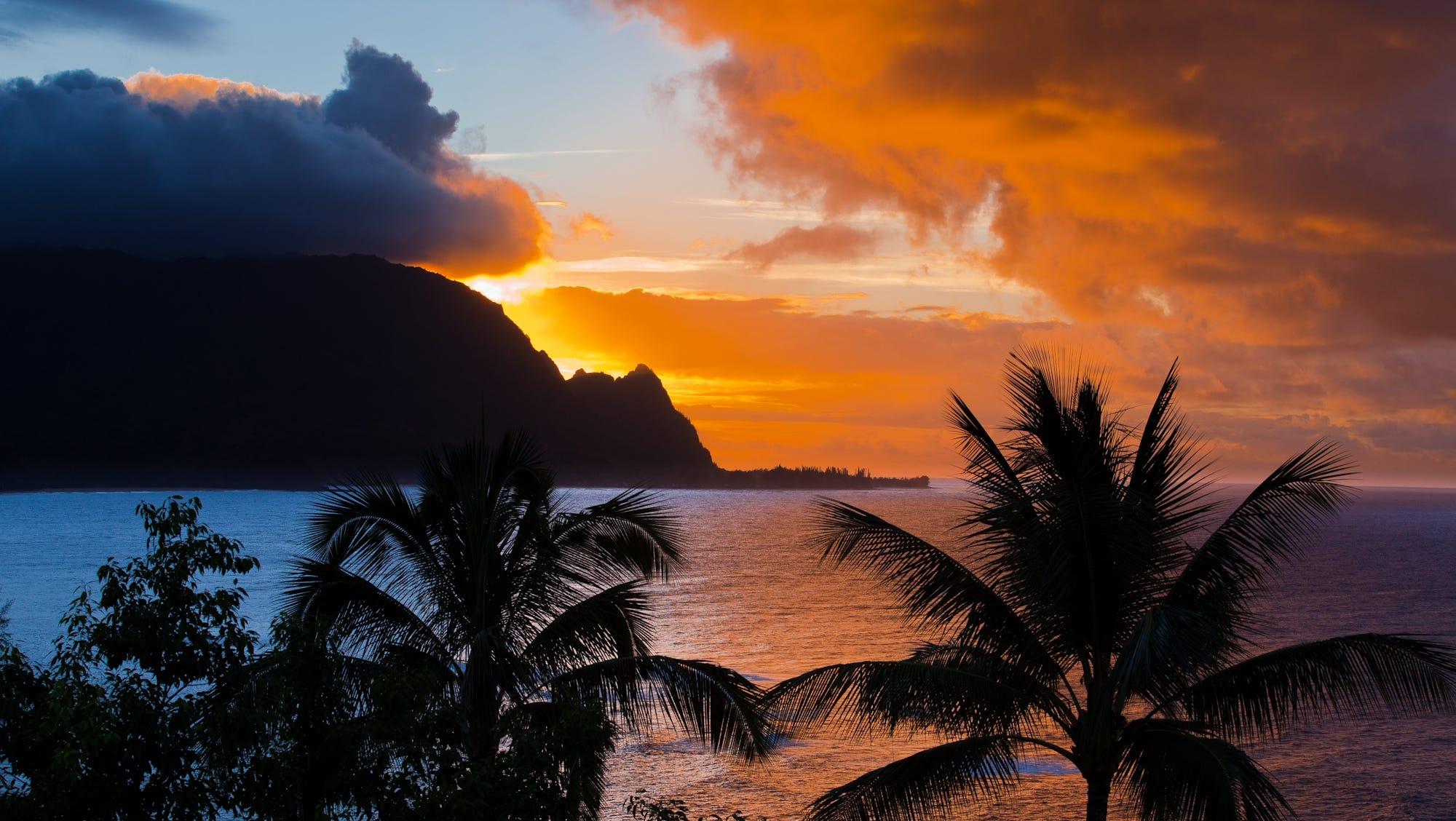 A vivid Kauai sunset illuminates the mountains lining the shore.