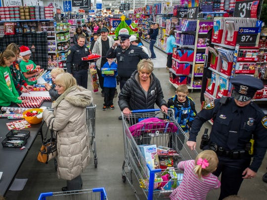 Police officers from Altoona and Pleasant Hill along with Polk County Sheriff's deputies made a lot of kids smile at their annual Cops 4 Kids Shop with a Cop event held at the Altoona Walmart Dec. 12. The men and women in blue and brown escorted area children in shopping for their own Christmas gifts.