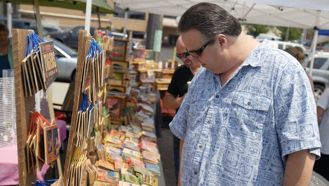 Scott Miller, of Marysville, looks over some decorative signs during the Art on the River event along the Black River in Port Huron.